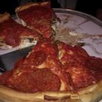 Deep dish pizza, asi tři centimetry vysoká, plná sýra a zeleniny